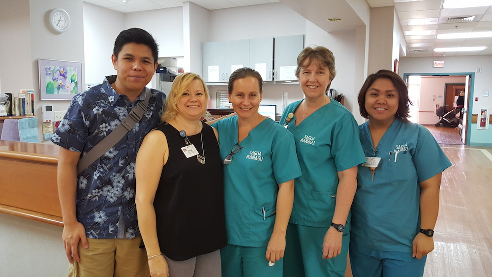 Adrian Medina pictured with FNU alum Teresa Anderson and birth center nurses.